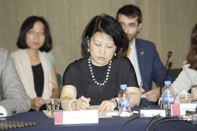 Xiao Yan toma notas durante la mesa redonda.