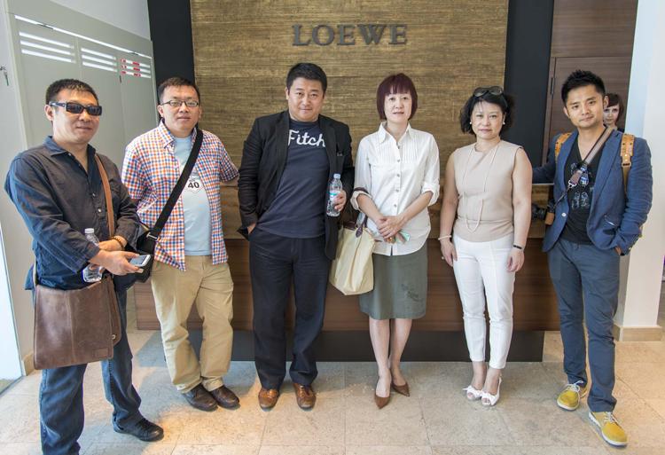 Los líderes chinos posan a la entrada de la fábrica de la marca de moda.